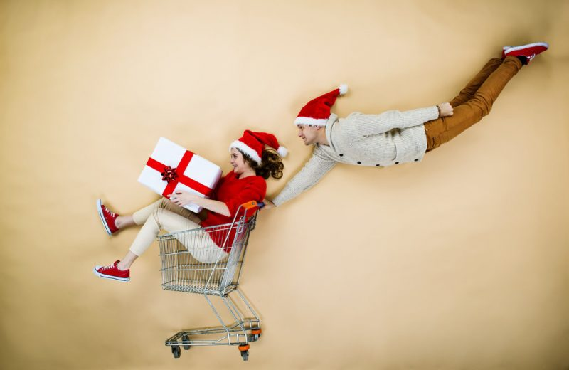 rsz graphicstock young couple in christmas hats having fun running with shopping trolley against the beige background srmdwa4nzw e1509640715170 - Christmas couple with trolley on beige background